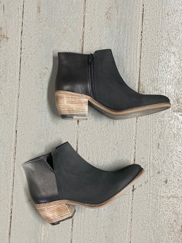 A pair of black microsuede booties with a wooden heel on a wooden background.