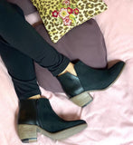 A pair of black microsuede booties with a stacked wooden heel on a woman's feet. Pink and purple fabric background.