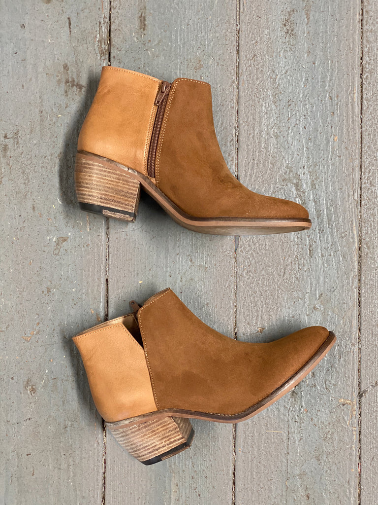 A pair of tan microsuede booties with a wooden heel on a wooden background.