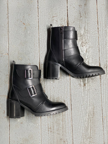 A pair of black vegan leather boots with a heel on a wooden floor. 2 large silver buckles on side, inside zipper closure.