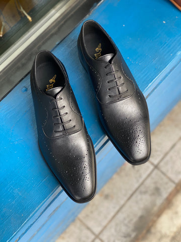 A pair of black vegan leather men's dress shoes with subtle perforated detailing. Lace up closure with 5 eyelets. Slightly tapered squared toe.