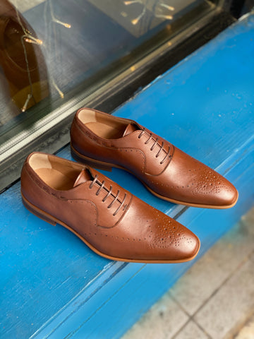 A pair of tan vegan leather men's dress shoes with subtle perforated detailing. Lace up closure with 5 eyelets. Slightly tapered squared toe. Tan sole.