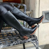 Knee high black vegan leather boots with a dark brown wooden heel and platform. Slightly pointed toe. On a woman's feet with iron bench in background.