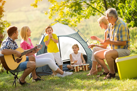 Family singing around campsite