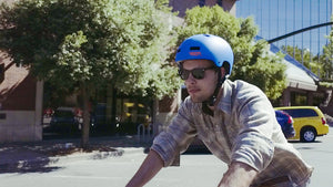 Young Man riding his bike in the city wearing a blue helmet, sunglasses and flannel shirt