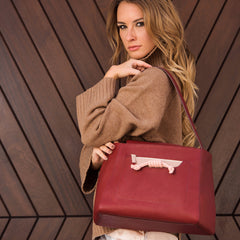 A model wearing light grey convertible leather tote bag for work with detachable clutch in front.