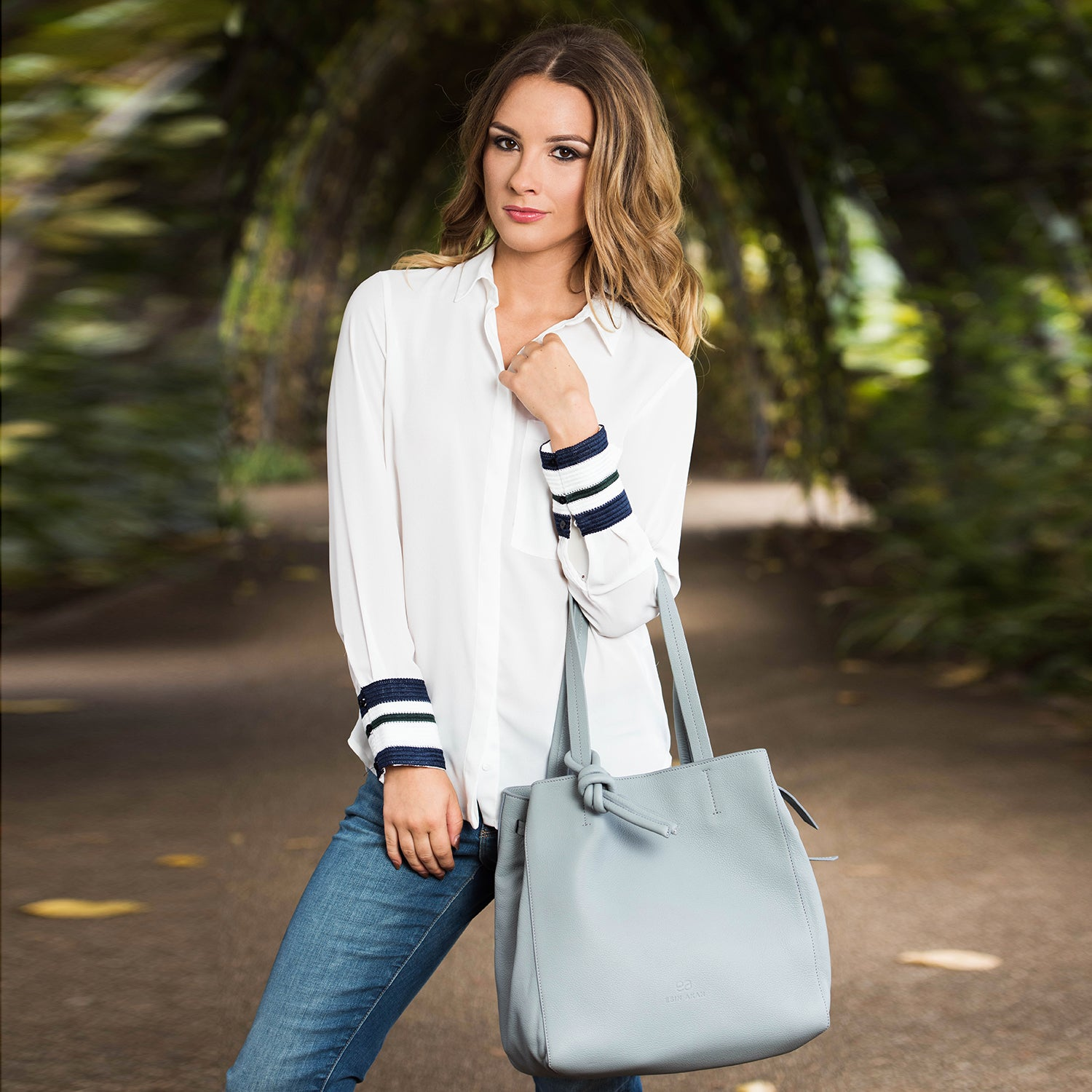A model wearing leather tote bag for women in navy.