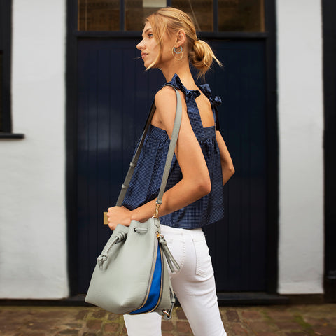 Model wearing a convertible medium leather bucket crossbody bag in grey and blue.