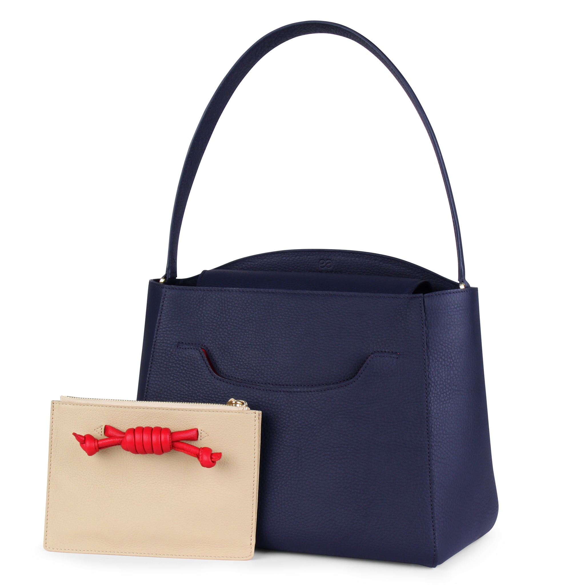 A navy convertible leather tote bag for work with a red and nude detachable clutch in front, front image.