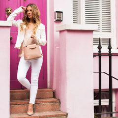 A model wearing pink convertible leather top handle tote bag as a handheld mini tote bag.