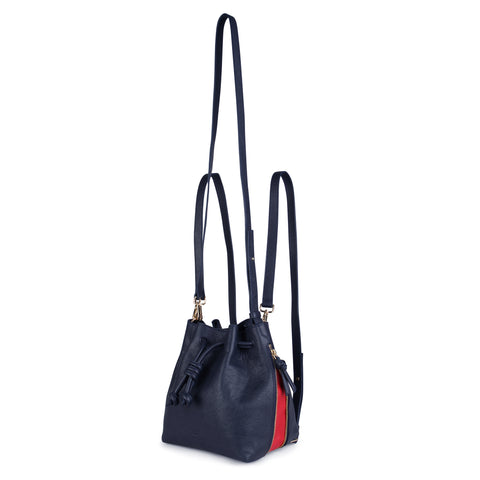 A convertible medium leather bucket crossbody bag in navy and red that could be used as a backpack, front image.