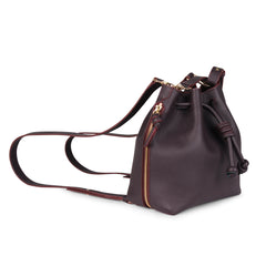 A convertible medium leather bucket crossbody bag in burgundy and pink that could be used as a backpack, zippers closed, side image.