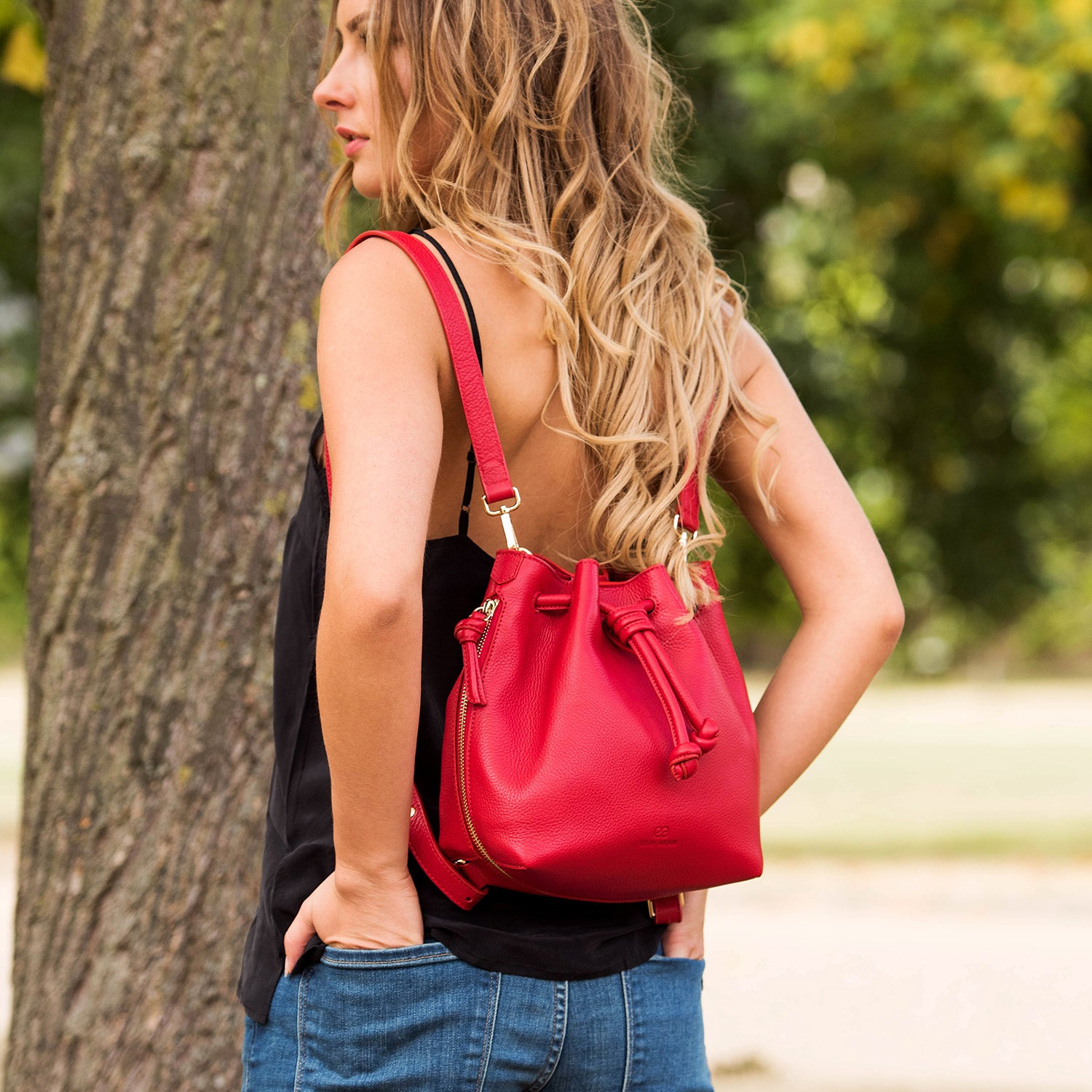 Model wearing a convertible medium leather bucket crossbody bag in red as a backpack.