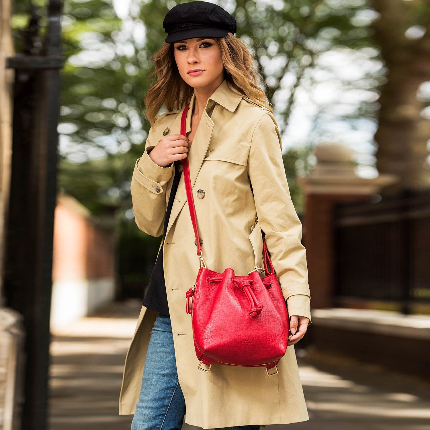 Model wearing a convertible medium leather bucket crossbody bag in red.