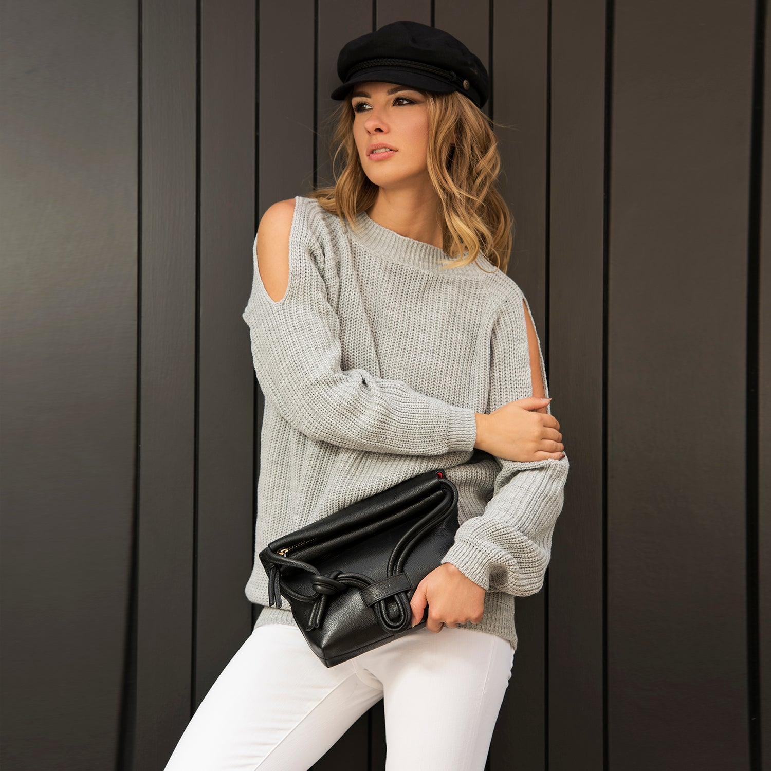 A model wearing convertible leather small black shoulder bag as a evening clutch using its roll down feature.