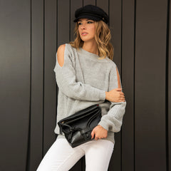 A model wearing light grey convertible leather small shoulder bag as a evening clutch using its roll down feature.