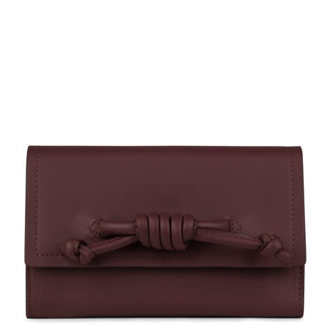 A convertible leather burgundy phone wallet with a knot detail in front that could be used as a crossbody bag, front image.