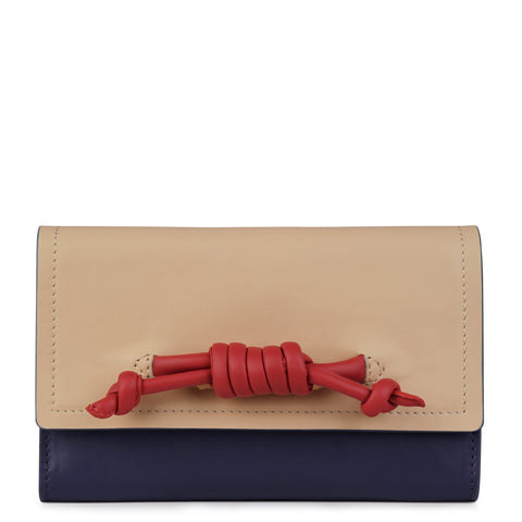 A convertible leather navy, nude and red phone wallet with a knot detail in front that could be used as a crossbody bag, front image.