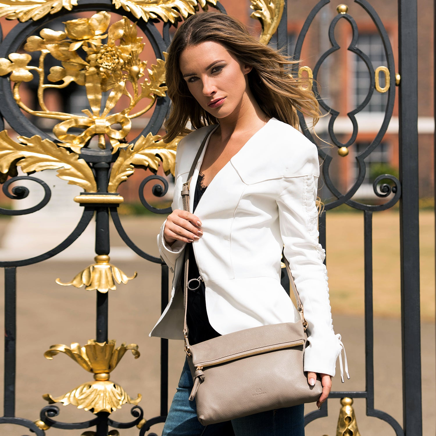 A model wearing brown convertible leather crossbody bag.