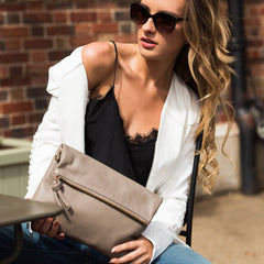 A model wearing brown convertible leather crossbody bag for women as an evening clutch.