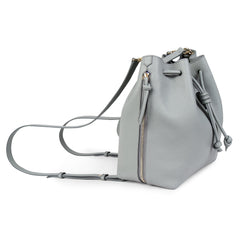 A convertible laptop size womens leather backpack in light grey that could be used as a crossbody as well as a bucket bag, side image.