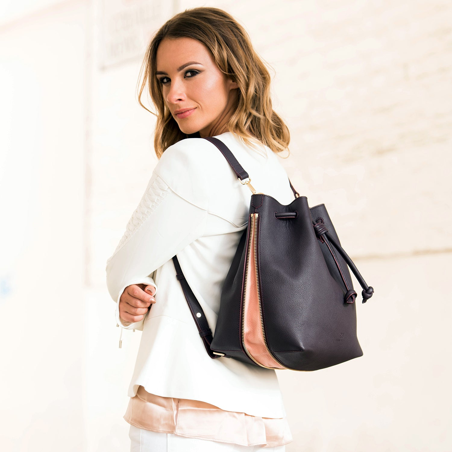 Model wearing a convertible laptop size leather black bucket bag as a backpack.