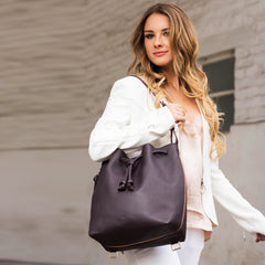 Model wearing a convertible laptop size leather bucket bag in grey as a shoulder bag.