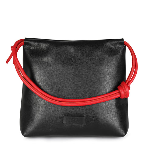 A convertible leather red and black shoulder bag for women with a knot detail on the strap that could be used as a clutch bag with its roll down feature, front image.