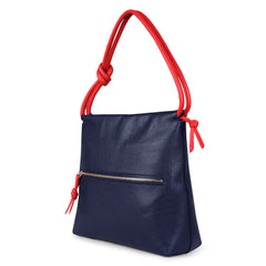 A convertible leather red and navy shoulder bag for women with a knot detail on the strap that could be used as a clutch bag with its roll down feature, side image.