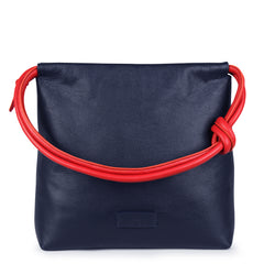 A convertible leather red and navy shoulder bag for women with a knot detail on the strap that could be used as a clutch bag with its roll down feature, front image.