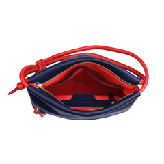 A convertible leather red and navy shoulder bag for women with a knot detail on the strap that could be used as a clutch bag with its roll down feature, interior image.