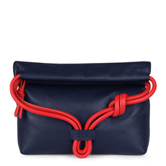 A convertible leather red and navy shoulder bag for women with a knot detail on the strap shown as a clutch bag, front image.