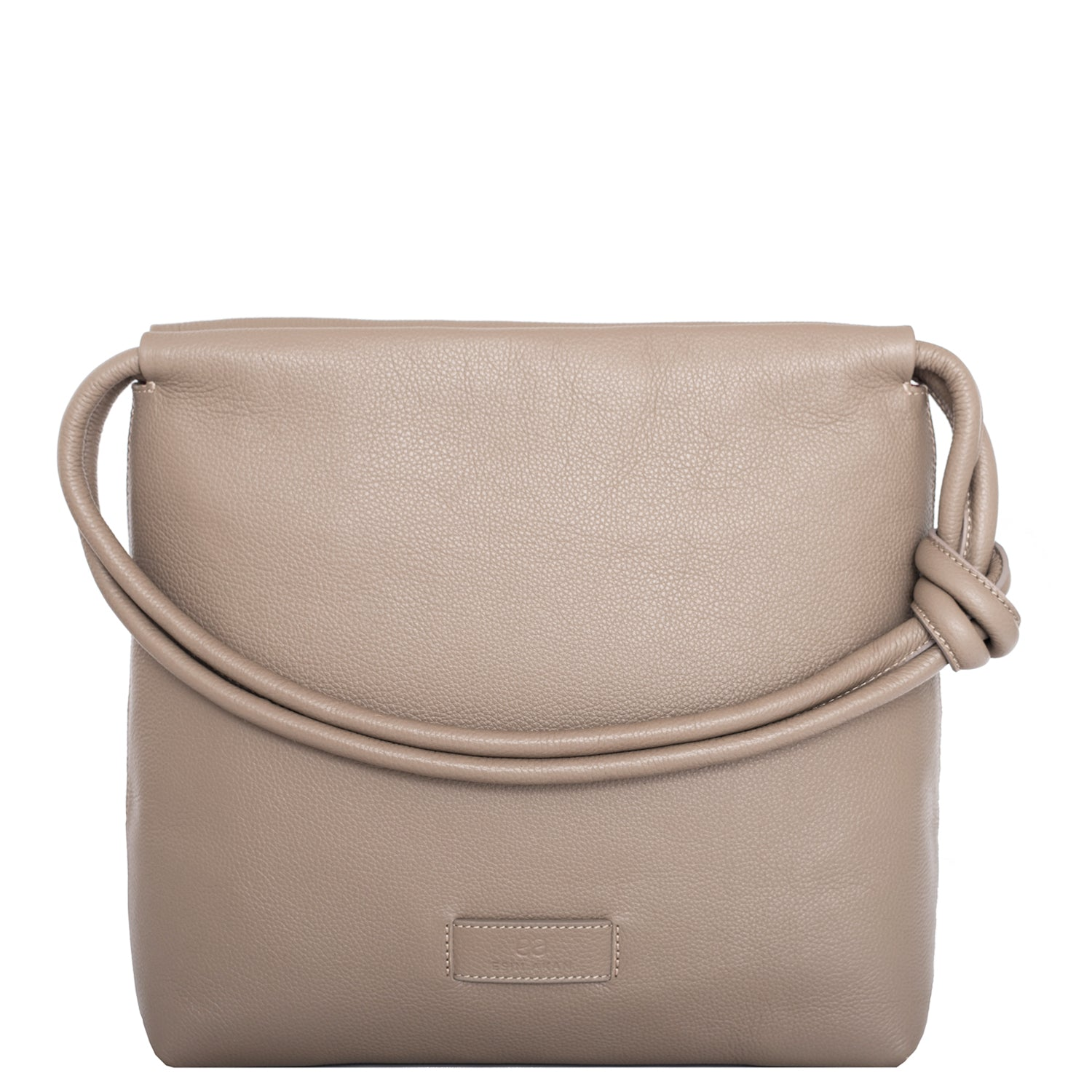 A convertible leather nude shoulder bag for women with a knot detail on the strap that could be used as a clutch bag with its roll down feature, front image.