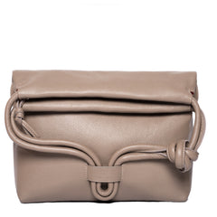 A convertible leather nude shoulder bag for women with a knot detail on the strap shown as a clutch bag, front image.