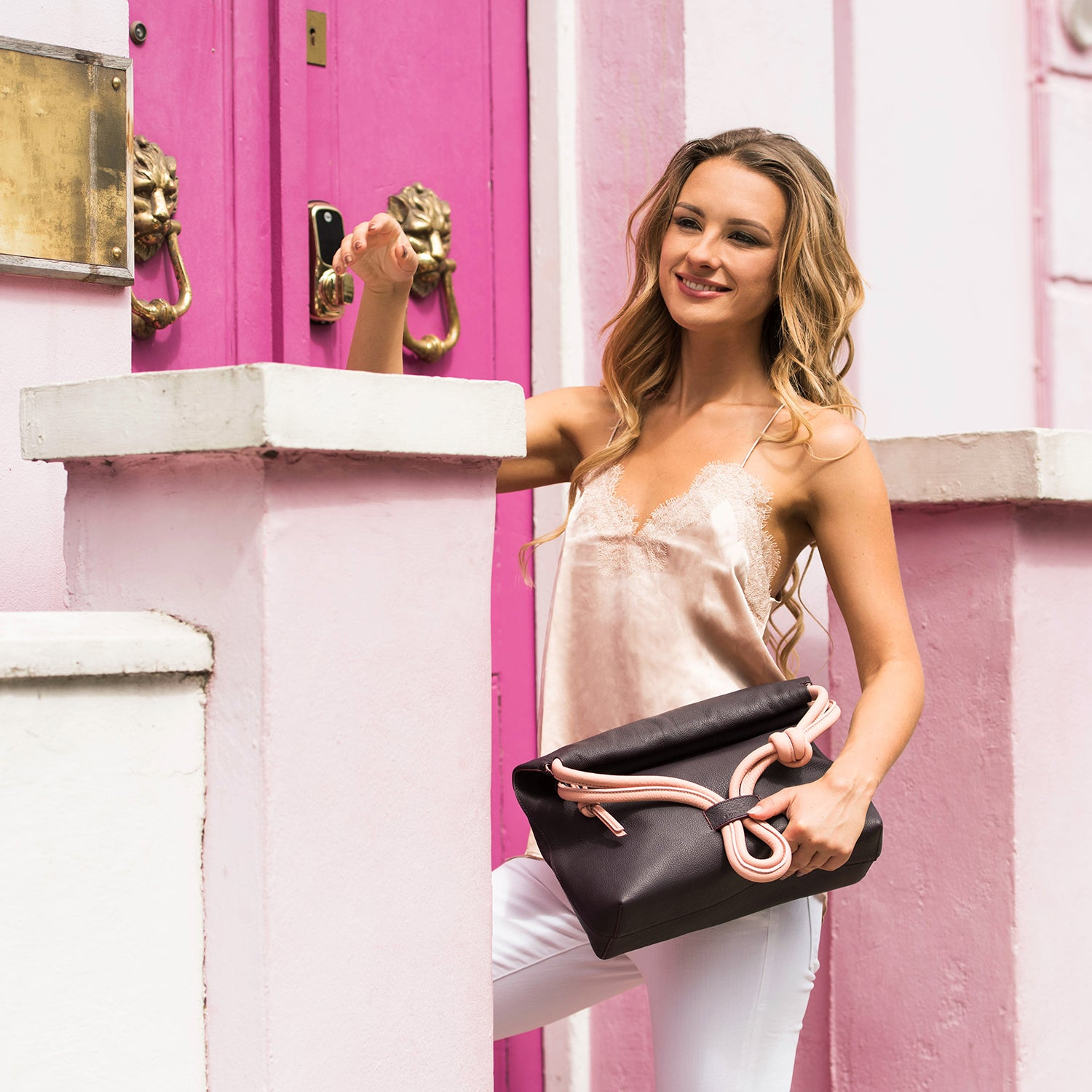 A model wearing convertible leather pink shoulder bag for women as an evening clutch using its roll down feature.