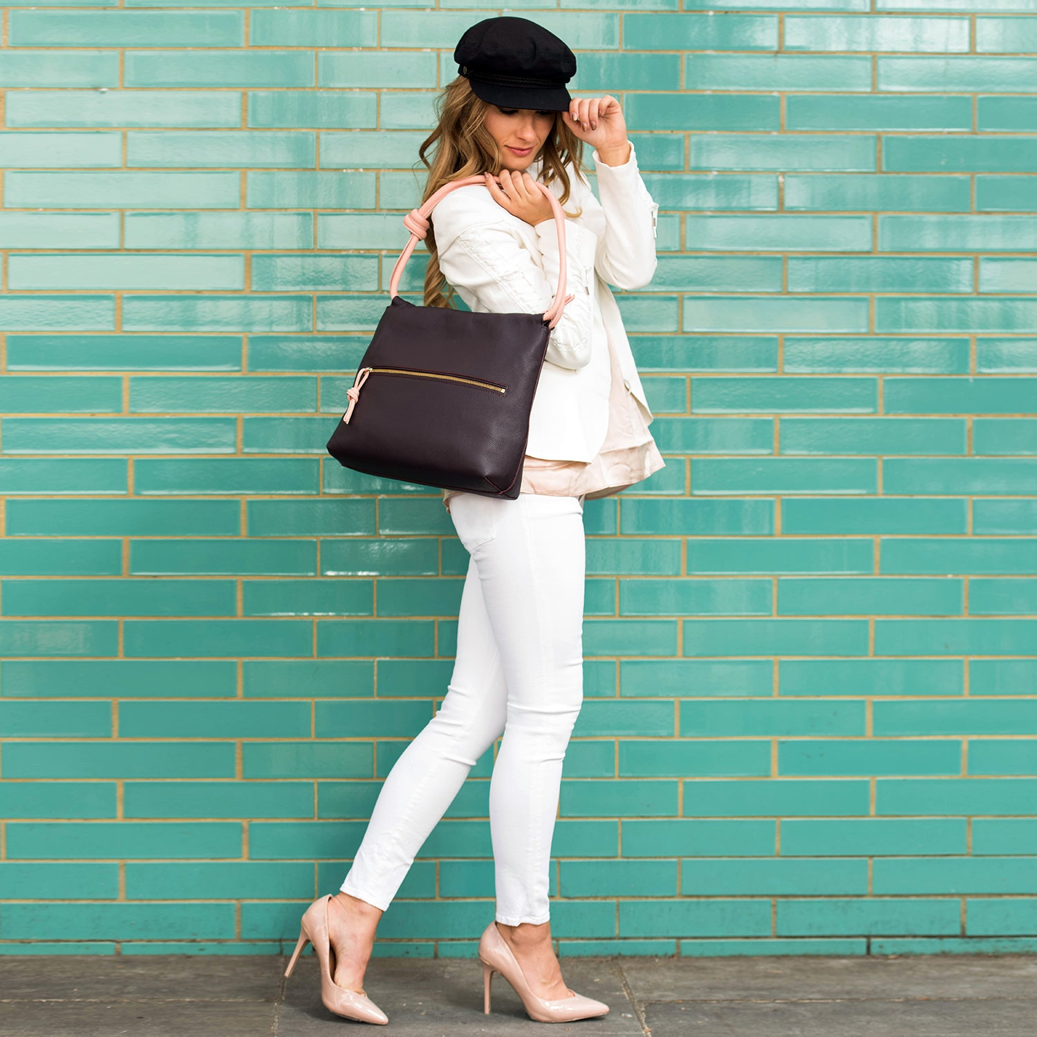 A model wearing convertible leather blue and grey shoulder bag for women.