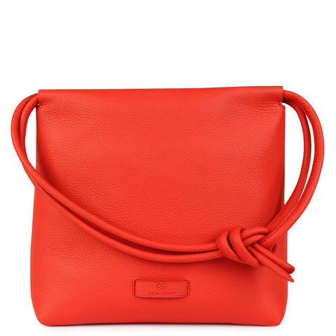 A convertible leather red shoulder bag for women with a knot detail on the strap that could be used as a clutch bag with its roll down feature, front image.
