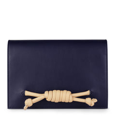 A convertible leather navy clutch bag with a knot detail in front that could be used as a crossbody bag, front image.