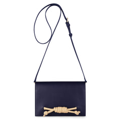 A convertible leather navy clutch bag with a knot detail in front shown as a crossbody bag, front image.
