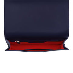 A convertible leather navy clutch bag with a knot detail in front that could be used as a crossbody bag, interior image.