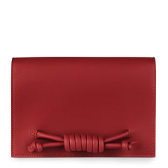 A convertible leather red clutch bag with a knot detail in front that could be used as a crossbody bag, front image.
