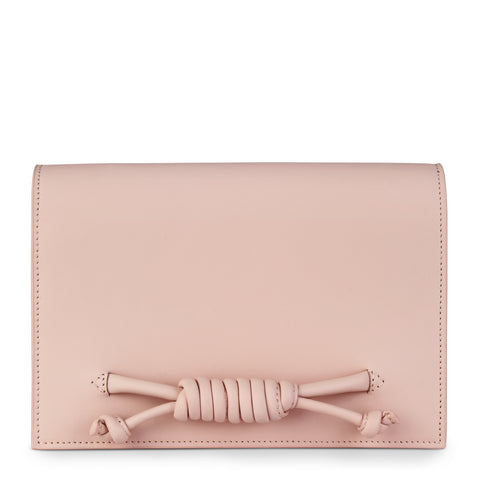 A convertible leather pink clutch bag with a knot detail in front that could be used as a crossbody bag, front image.