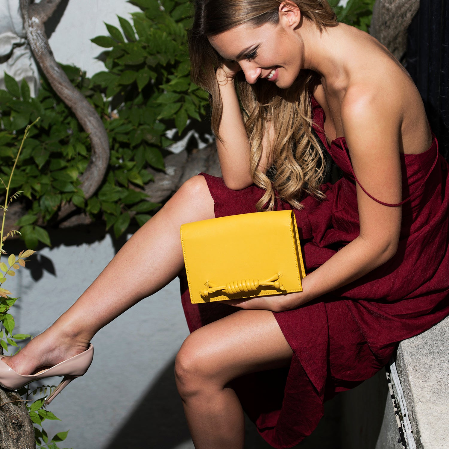 A model wearing convertible leather navy clutch bag as a clutch.