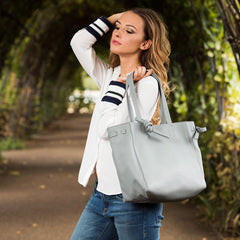 A model wearing leather tote bag for women in nude as a travel bag.