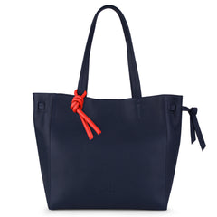 An expandable leather tote bag for women in navy and red shown as a travel bag, front image.