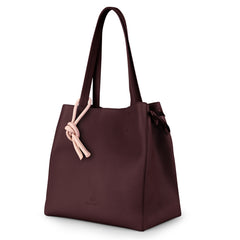 An expandable leather tote bag for women in burgundy and pink that could be used as a travel bag, side image.