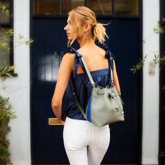 Model wearing a convertible medium leather bucket crossbody bag in grey and blue as a backpack.