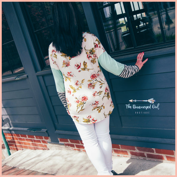 Woman wearing a spring mint color block top showing the back which is ivory with peach and rose color florals with green foliage. The-Brown-Eyed-Girl -Products