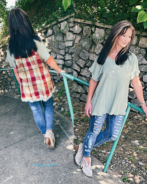 Woman wearing a sage mint short sleeve tunic with fall harvest plaid back.