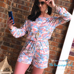 Woman wearing a pink and blue camo print long sleeve romper. Featuring a slimming fit with a cinched waist. This item fits true to size and can be worn on or off the shoulder. Model size 7 wearing a medium.
